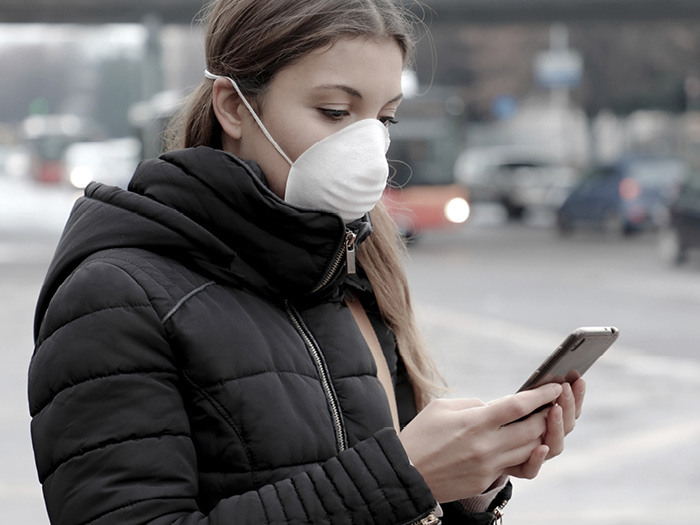Atradius | Young female on a phone wearing a face mask